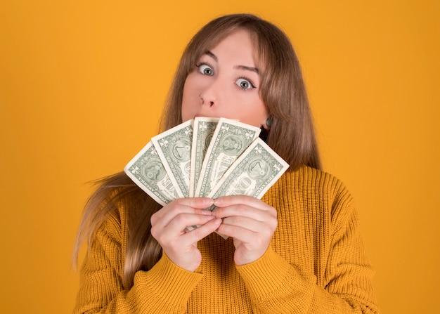 Счастливая женщина с много счетов в ее руках на желтом фоне