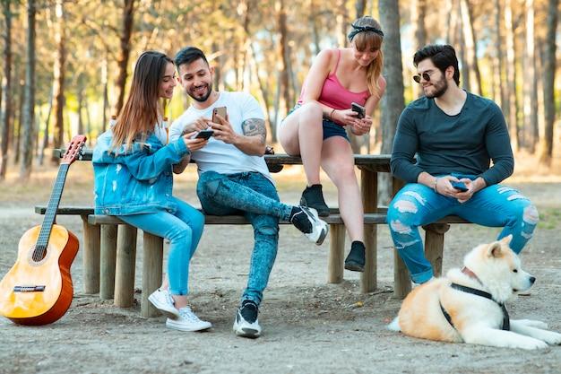 Счастливые друзья веселятся на природе на пикнике, молодые люди радуются пиву и гитаре в выходные дни летом - дружба