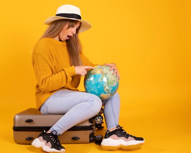Портрет счастливая женщина, путешественник с глобусом и чемоданом, на желтом пространстве