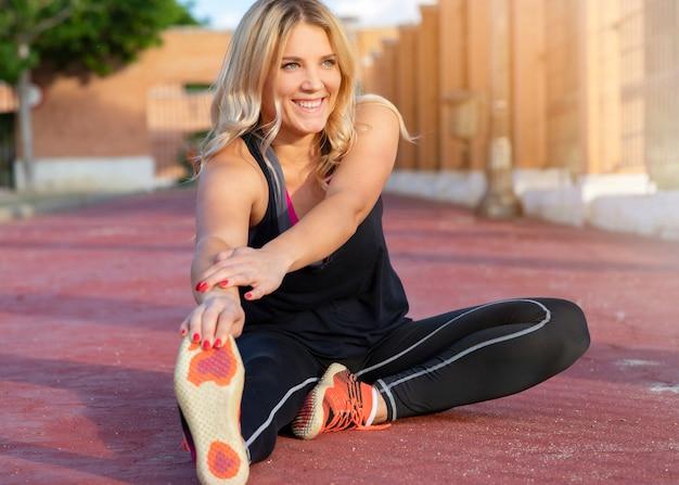 女性は屋外で地面にストレッチスポーツをします