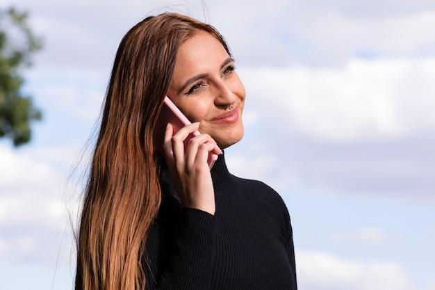 かなり若い女性は屋外に笑みを浮かべて彼女の電話で話す