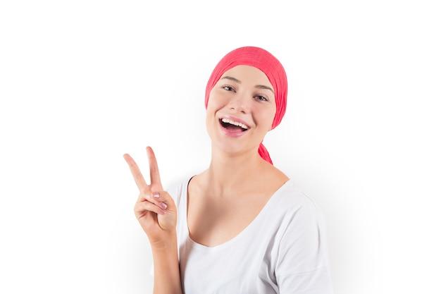 彼の頭にピンクのスカーフ、癌に対する勝利を持つ若い男