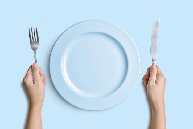 Голубая плита с серебряной вилкой и нож на голубой предпосылке с путем клиппирования.