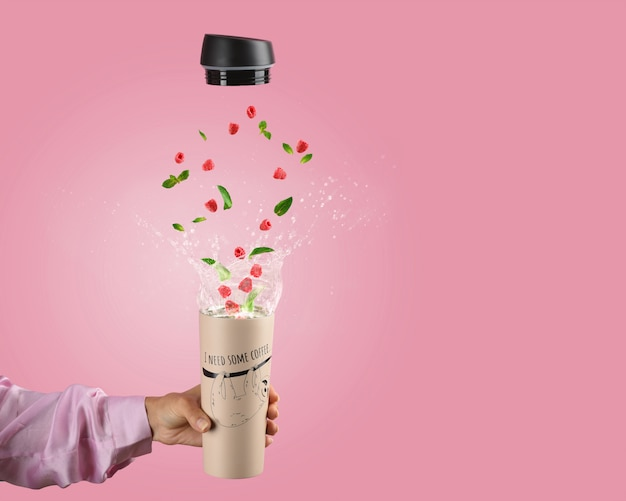 Женская рука держит кружку термоса с разбрызгивания горячего чая и летающих малины и листьев мяты на розовом фоне