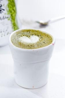ハート形の泡と白いマグカップの抹茶ラテ