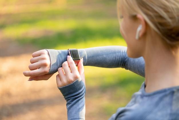 スポーツウーマンが時計またはフィットネスブレスレットのトレーニングモードをオンにして実行を開始する