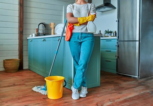 Очистка. обрезанное изображение привлекательной женщины в повседневной одежде и защитных перчатках с тряпкой и спреем в руках, шваброй и ведром возле нее собираются на генеральную уборку на кухне.