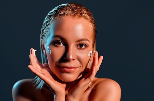 Красивая женщина наносит крем для лица