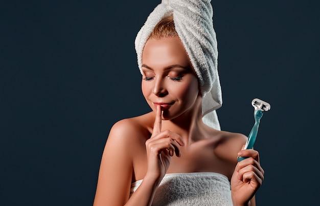 Портрет молодой привлекательной женщины с полотенцем на ее голове, держащей бритву на черной стене.