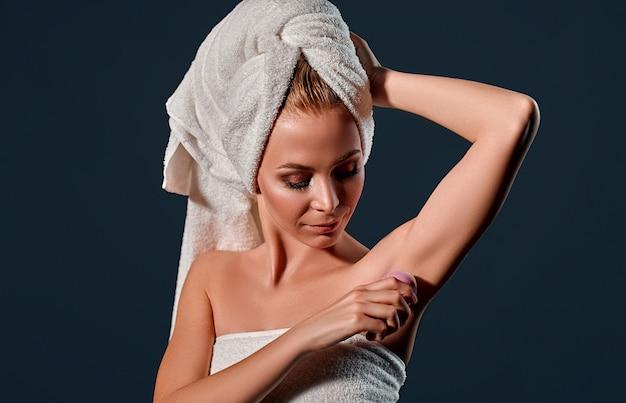 Портрет молодой привлекательной женщины с полотенцем на голове использует шариковый антиперспирант на черной стене.