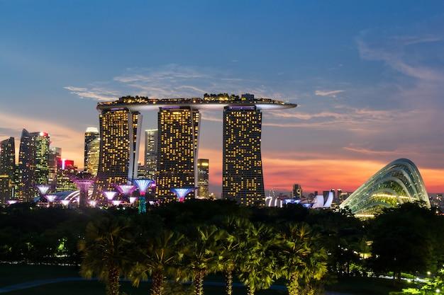 Городской пейзаж сингапура на пристани и закат в сумерках