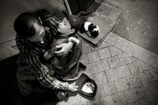 Бездомный человек с ребенком и щенком