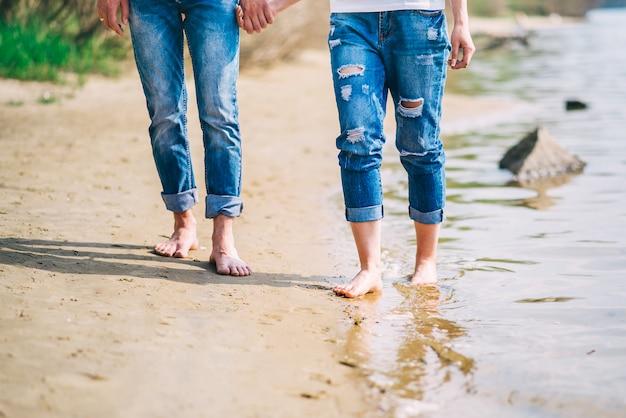 ビーチに沿って歩く若い裸足のカップル。水の夏の足