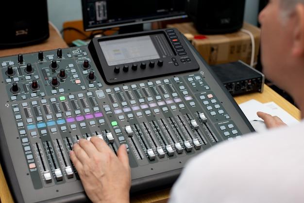 Смеситель пульт для записи звука. звукорежиссер за работой в студии. усилитель звука микшерный пульт эквалайзер. диджей