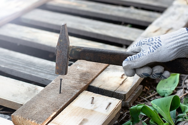 Плотник забивает гвоздь