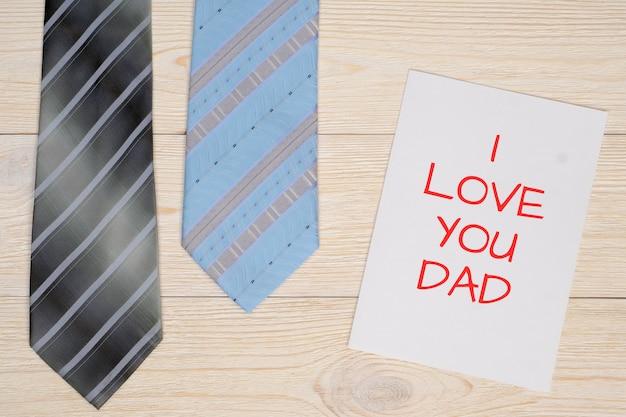 Я люблю тебя папа сообщение на листе бумаги и два галстука на белом деревянном столе