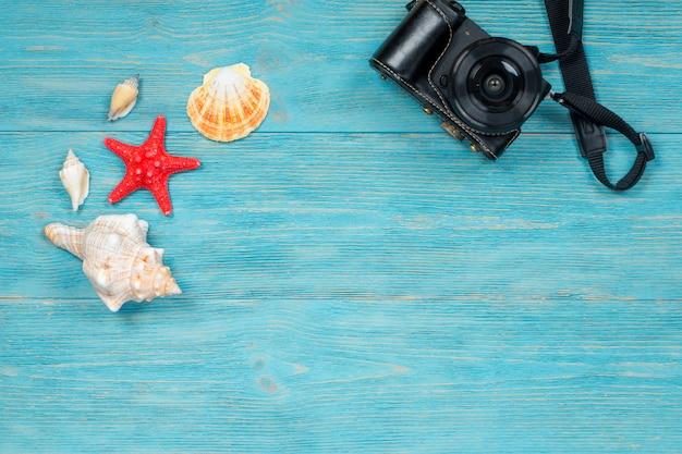 貝殻や木製の板の上の写真のカメラ