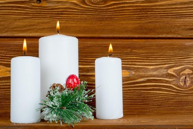 木製の背景にパインブランチと白いキャンドル