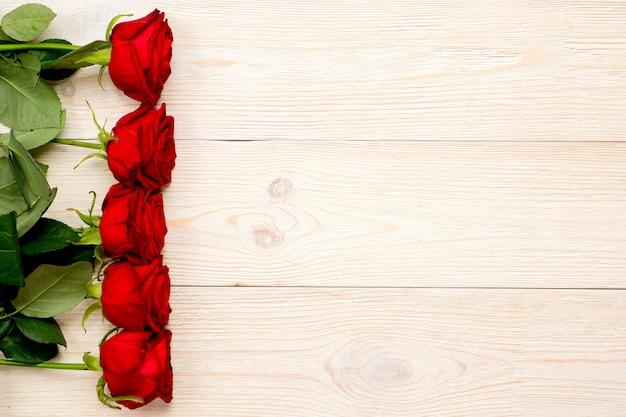 白い机の上の縦の行に赤いバラ、バレンタインのポストカード