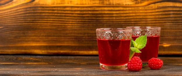 赤い自家製ラズベリーワインやお酒、木製のテーブルにミント