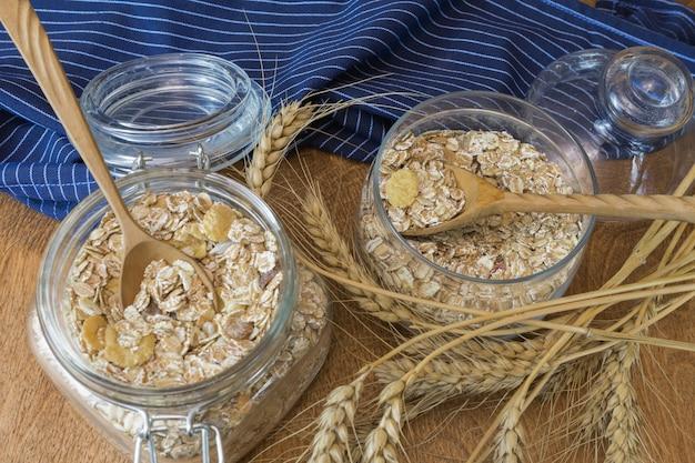 ミューズリー、朝食用シリアル、木製テーブルの上のガラス容器でオートミール。素朴な食べ物。