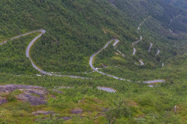 Серпантин в горах норвегии, хмурая погода, мокрый асфальт.