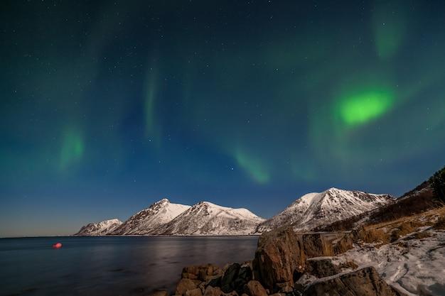 北ヨーロッパ-ロフォーテン諸島、ノルウェーの山々の上の美しいオーロラ、極光、