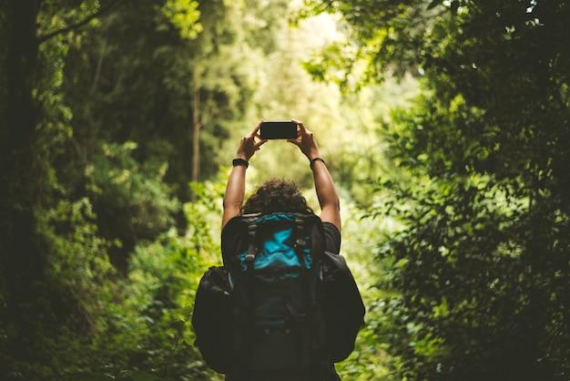 彼の携帯電話で風景の写真を撮るバックパックを持つハイカー。