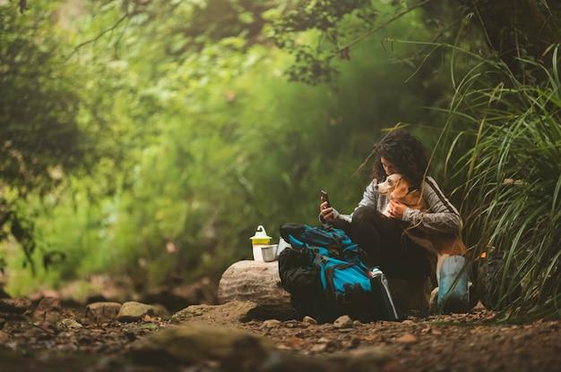 彼女の犬と一緒に歩いて、休んで、自然を楽しんでいるハイカーの女の子。