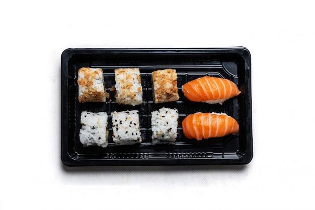Поднос с суши калифорния ролл и маки на черный поднос, расположенный на деревянном столе. японское гастрономическое блюдо на переработке.