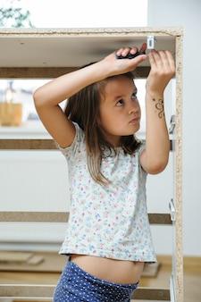 Девушка с помощью отвертки крутит винты в мебели.