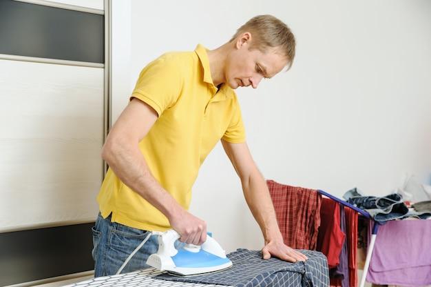 Мужчина гладит рубашку на гладильной доске