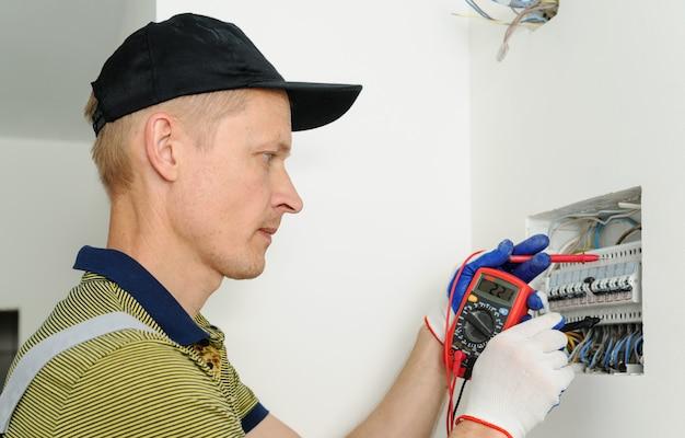 電気技師は電気ヒューズボックスの電圧を確認します。