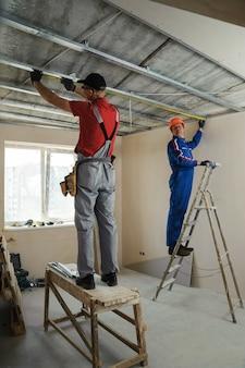 労働者は金属フレームを測定します