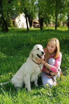美しい女性と公園で犬