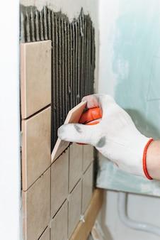 Рабочий кладет плитку на стену на кухне.