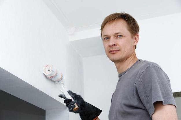 男は部屋の壁ローラーを描いています。