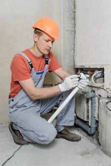 Рабочий устанавливает канализационные трубы.