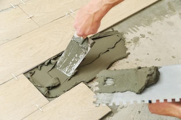 Рабочий кладет плитку на пол.