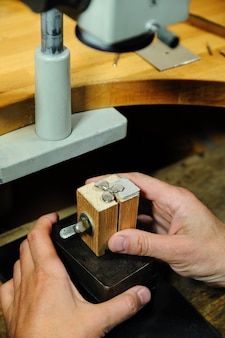 Изготовление ювелирных изделий. незавершенное золотое кольцо сжимается в деревянные тиски.