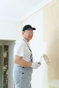 Художник красит стену в комнате.