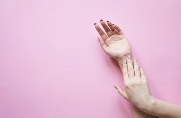 パステルに美しい女性の手。手の皮膚のケアのための自然化粧品、手のしわを減らし、保湿します。平面図とコピースペースフラットレイ