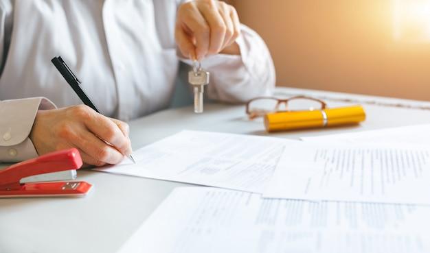 契約に署名した後、彼のクライアントに家の鍵を保持している不動産業者。不動産、ビジネス、不動産のコンセプト