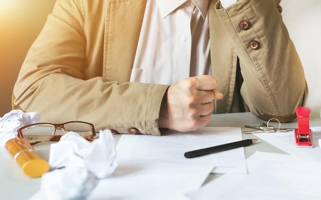 机に手で頭を座っている実業家には、しわくちゃの紙が覆われています。彼のビジネスで次に何をすべきかを知らない起業家失望、ビジネスの喪失の概念