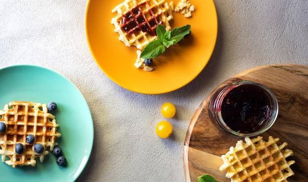 オレンジと緑のプレートにジャムとブルーベリーとクランベリーで満たされたデザートワッフル