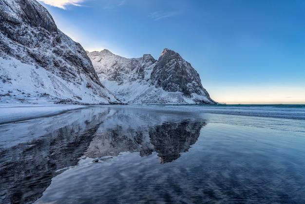 ノルウェーのロフォーテン諸島の水の山の反射と雪でいっぱいのビーチ