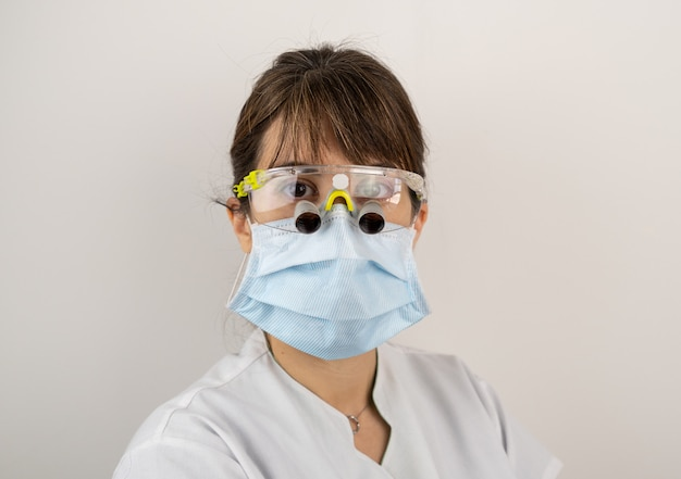 Женщина дантиста с лабораторным халатом в очках для удаления зубов