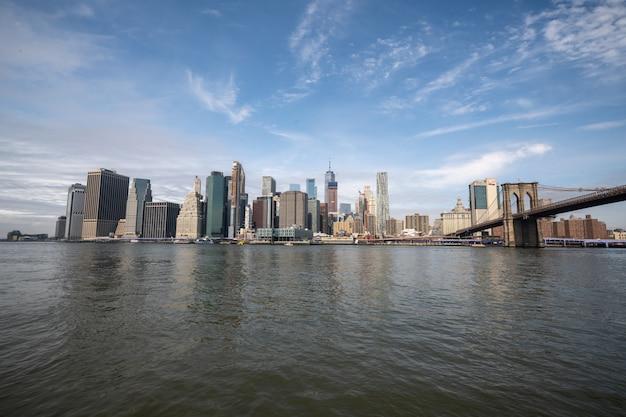 白昼のブルックリン橋でハドソン川のニューヨークのスカイライン反射
