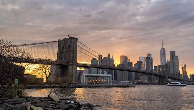 日没時のブルックリン橋でハドソン川にニューヨークのスカイライン反射