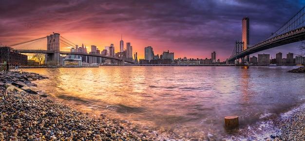 ブルックリンブリッジでハドソン川に架かるニューヨークのスカイライン反射と海岸の日没でマンハッタン橋